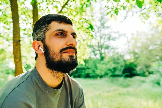 Portret młodego brodatego mężczyzny rasy kaukaskiej ze słuchawkami na zewnątrz z tłem roślinności