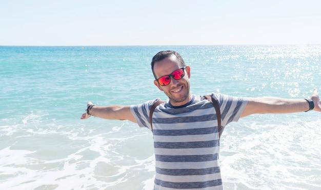 Portret młodego brodatego mężczyzny stojącego na brzegu morza w słoneczny dzień