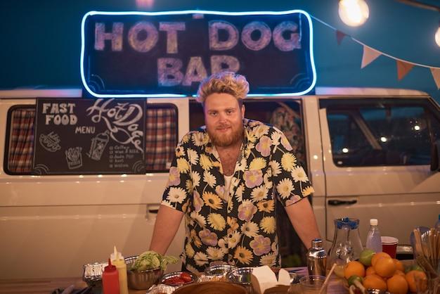 Portret młodego brodatego mężczyzny uśmiechającego się do kamery, który pracuje w barze na świeżym powietrzu podczas imprezy na plaży