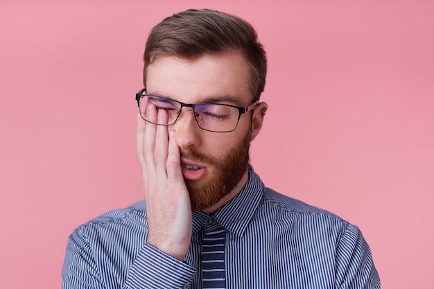 Portret młodego brodatego mężczyzny w okularach, zmęczony pracą i zasypianiem, podpierając głowę, na białym tle na różowym tle.