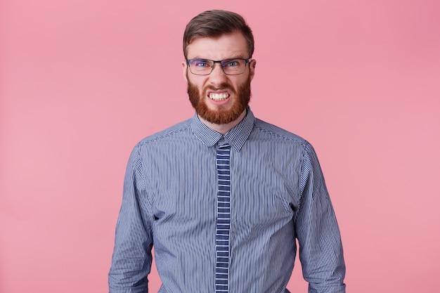 Portret młodego brodatego mężczyzny w pasiastej koszuli w okularach, zły i agresywnie obnaża zęby na białym tle na różowym tle.