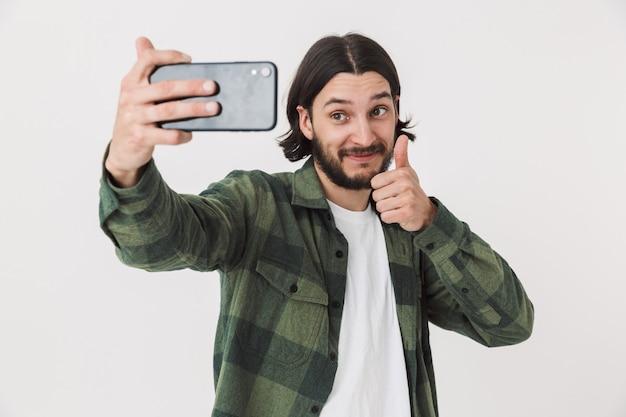 Portret młodego brodatego mężczyzny w zwykłych ubraniach, stojącego na białym tle nad ścianą, robiącego selfie, kciuk w górę