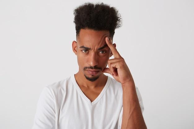 Portret młodego brunetki kręcone ciemnoskóry facet trzymając podniesioną rękę na głowie, patrząc zmęczony na aparat