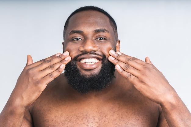Portret młodego brutalnego african american murzyn, stosując krem do twarzy na jego policzek na białym tle nad białym tle. bliska portret, męska uroda. ochrona skóry