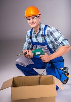 Portret młodego budowniczego z narzędziami w ręku.