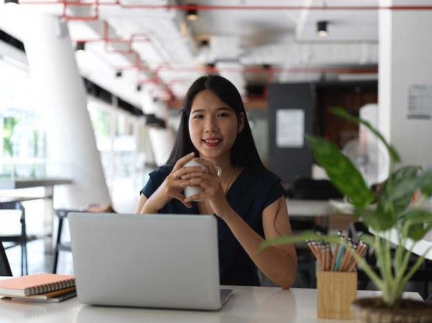 Portret młodego całkiem azjatyckiego bizneswoman patrząc w kamerę, trzymając filiżankę kawy w obszarze roboczym