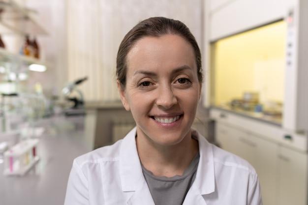 Portret młodego chemika w białym fartuchu uśmiecha się do kamery podczas pracy w laboratorium