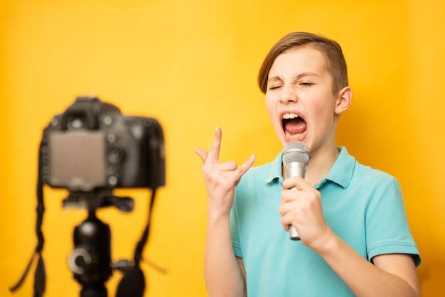 Portret młodego chłopca nastolatek śpiewa przez mikrofon na żółtym tle