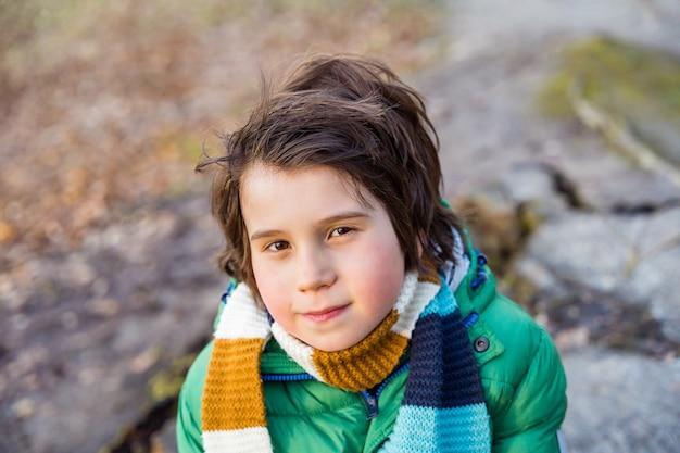 Portret młodego chłopca w wieku dziewięciu lat, ubranego w zieloną puchową kurtkę i szalik, spacerującego na świeżym powietrzu w parku lub lesie