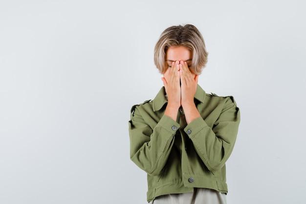 Portret młodego chłopca z rękami na twarzy w zielonej kurtce i przygnębionym widokiem z przodu