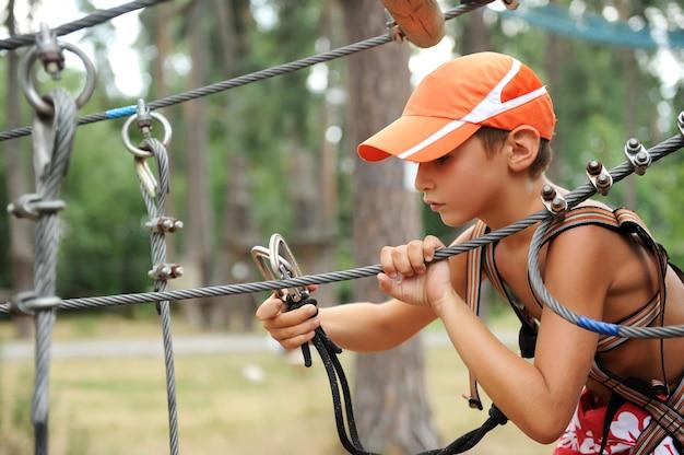 Portret młodego chłopca zaangażowany w wspinaczkę na park linowy.