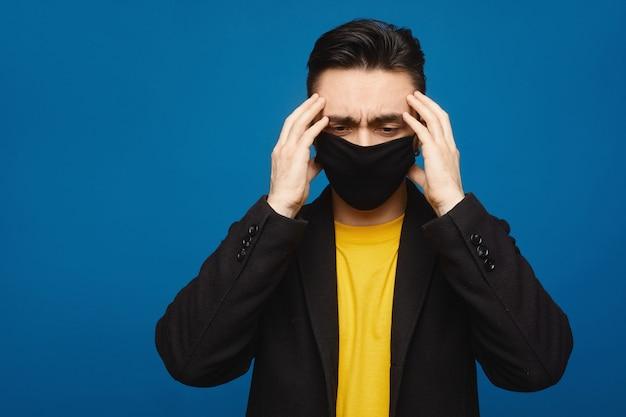Portret młodego chorego mężczyzny w czarnej masce ochronnej na twarzy cierpiących na bóle głowy i osłabienie