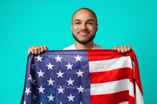 Portret młodego ciemnoskórego mężczyzny dumnie trzymając flagę usa na turkusie