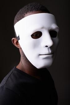 Portret młodego czarnego mężczyzny afrykańskiego w ciemnym pokoju na sobie maskę