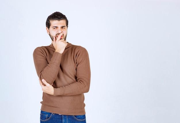 Portret młodego człowieka myślącego i stojącego przed białą ścianą.