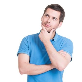 Portret młodego człowieka myślenia patrzy ręką w pobliżu twarzy