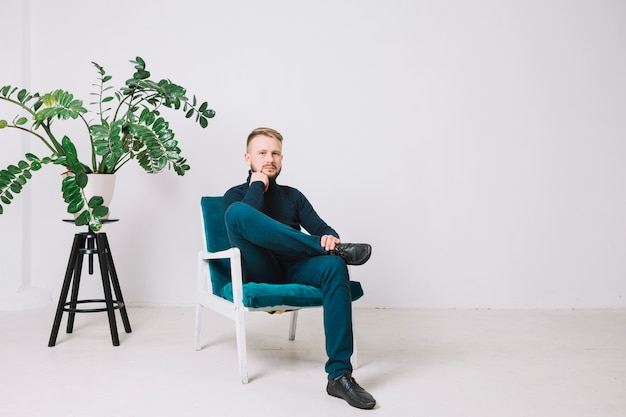 Portret młodego człowieka obsiadanie na krześle w biurze