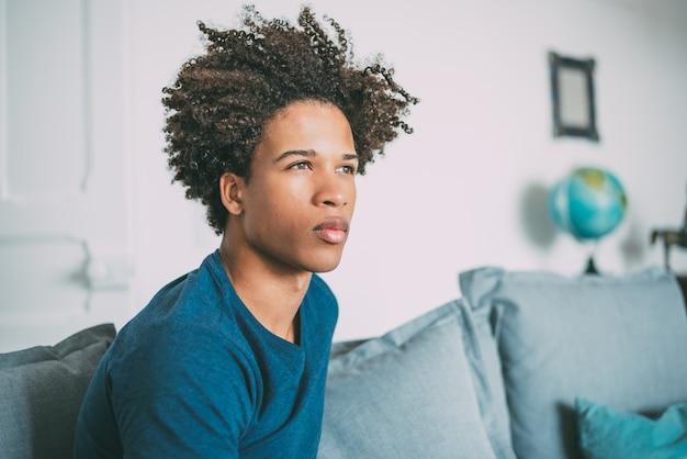 Portret młodego człowieka przemyślany rasy mieszanej siedzi na kanapie