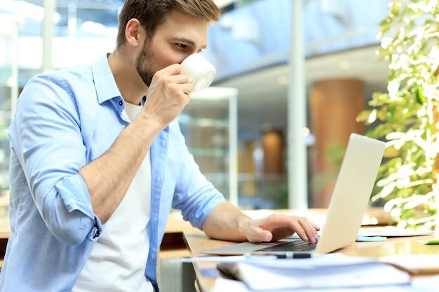 Portret młodego człowieka siedzącego przy biurku w biurze, picia kawy i pisania na laptopie.