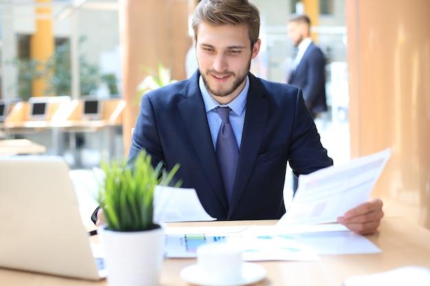 Portret młodego człowieka siedzącego przy biurku w biurze.