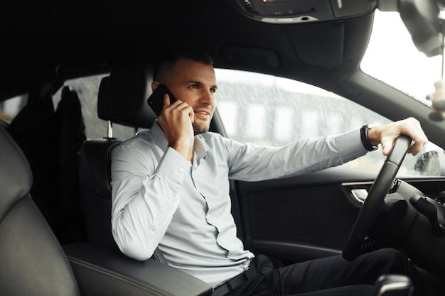 Portret młodego człowieka sukcesu w samochodzie. rozmowy i rozmowy telefoniczne, negocjacje.