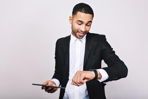 Portret młodego człowieka sukcesu zajęty w białej koszuli, czarnej kurtce, patrząc na zegarek z tabletem. stylowy biznesmen, zajęty, czas na pracę, spotkanie, przywództwo.