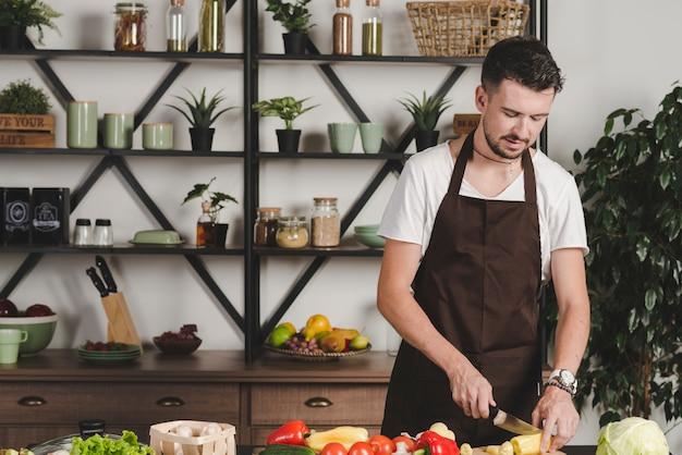 Portret młodego człowieka tnący warzywa z nożem w kuchni