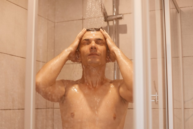 Portret młodego dorosłego człowieka, mycie skóry ciała i włosów pod prysznicem w domu, wnętrze łazienki. zdrowy, przystojny mężczyzna styl życia, dobre samopoczucie i pielęgnacja.
