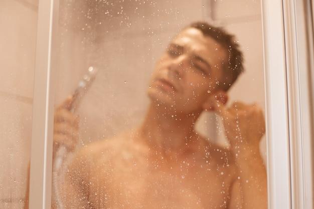 Portret młodego dorosłego mężczyzny o ciemnych włosach, mycie ucha podczas brania prysznica i stojąc pod wodą w kafelkowej łazience prysznic, poranne procedury higieniczne.
