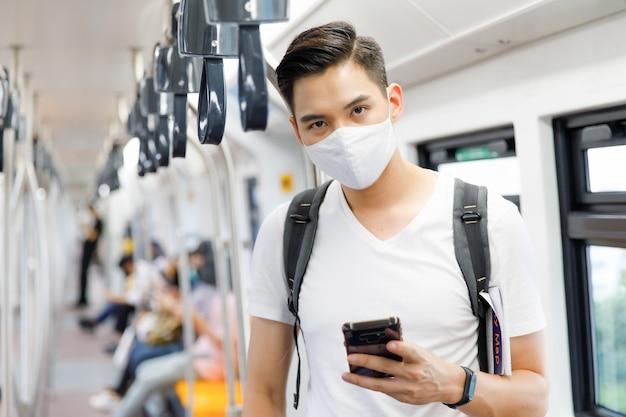 Portret młodego dorosłego mężczyzny z azji w masce medycznej, stojącego, trzymającego smartfon i patrzącego na kamerę w pociągu skytrain z rozmytym tłem skytrain. nowa koncepcja normalnego stylu życia