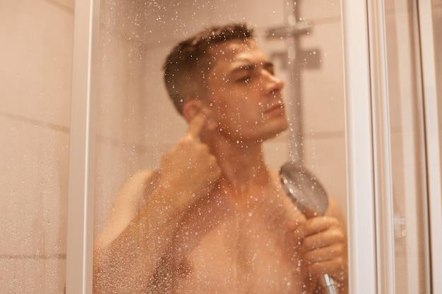 Portret młodego dorosłego przystojny ciemnowłosy mężczyzna, czyszczenie ucha podczas brania prysznica i stojąc pod bieżącą wodą w nowoczesnej łazience wyłożonej kafelkami.