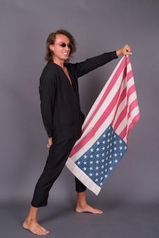 Portret młodego dumnego mężczyzny amerykańskiego trzymającego flagę usa