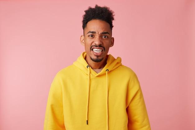Portret młodego dziwacznego afroamerykanina w żółtej bluzie z kapturem, marszczącego brwi i niezrozumienie tego, co się dzieje, brzydko wyglądający.