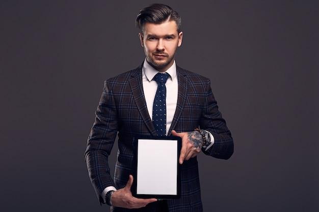 Portret młodego eleganckiego brutalnego mężczyzny z tabletem