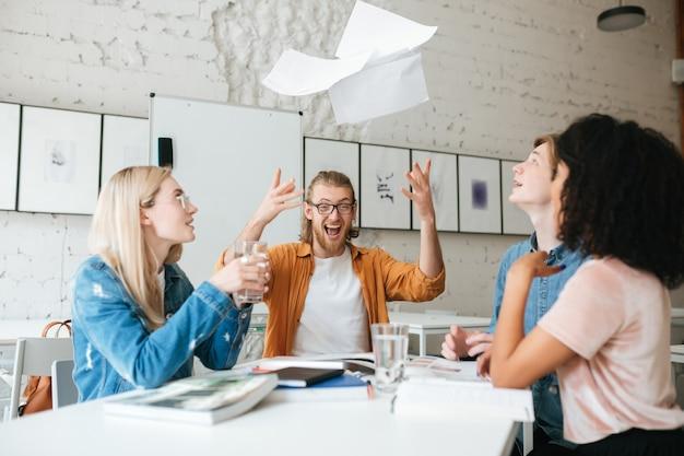 Portret młodego emocjonalnego chłopca z blond włosami i brodą szczęśliwie rzucać papierami siedząc z przyjaciółmi. grupa ludzi pracujących razem