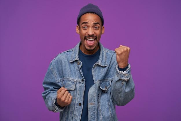 Portret młodego, energetyzowanego, dość ciemnoskórego, brodatego mężczyzny, który podnosi radośnie pięści i krzyczy radośnie z otwartymi szeroko ustami, odizolowany na fioletowej ścianie