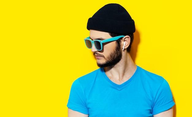 Portret młodego faceta hipster za pomocą słuchawek bezprzewodowych, na sobie niebieską koszulę