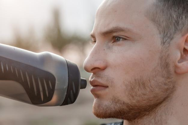 Portret młodego faceta rasy białej wody pitnej z butelki po treningu lub przed treningiem