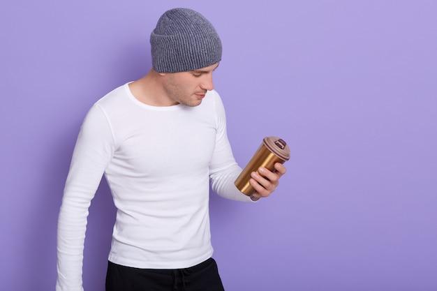 Portret młodego faceta, stojącego i trzymającego kubek termiczny, idącego w kierunku zerowego marnotrawstwa, pozującego na bzu, mężczyzna ubrany w białą koszulę i szarą czapkę. skopiuj miejsce na reklamę.