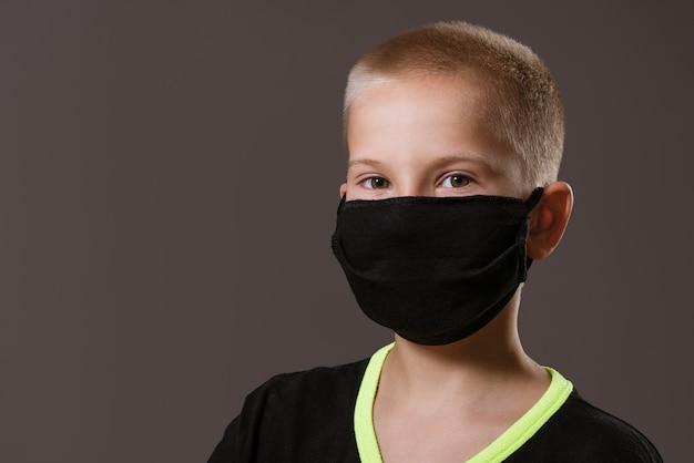 Portret młodego faceta w czarnej masce ochronnej i koszulce na szarej ścianie