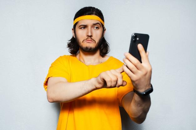 Portret młodego faceta z pomarańczową koszulką, trzymającego smartfona na białym tle