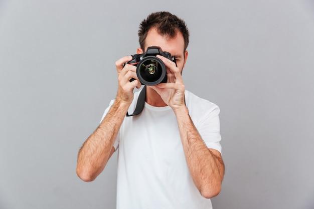 Portret młodego fotografa z aparatem na szarym tle