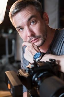 Portret młodego fotografa z aparatem w studio