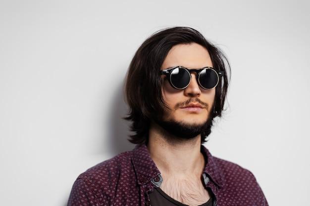 Portret młodego hipster na sobie okrągłe okulary przeciwsłoneczne.