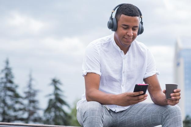 Portret młodego i szczęśliwego african american człowieka ze słuchawkami. mężczyzna siedzący na ławce i słuchający muzyki, trzymający smartfon i kubek kawy