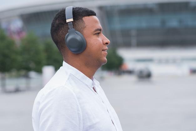 Portret młodego i szczęśliwego african american człowieka ze słuchawkami. osoba słuchająca muzyki