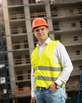 Portret młodego inżyniera budowlanego stojącego na placu budowy