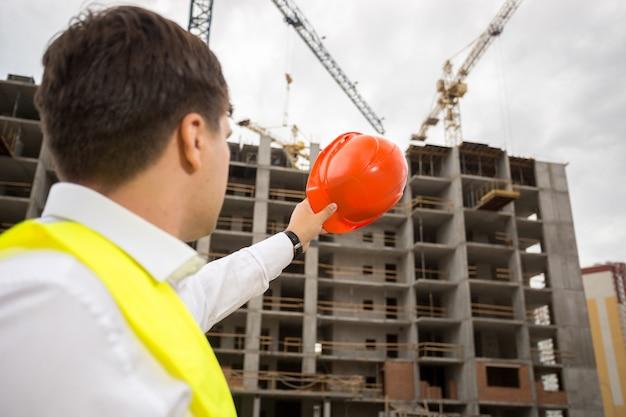 Portret młodego inżyniera budowlanego wskazującego na budynek w budowie z czerwonym kaskiem