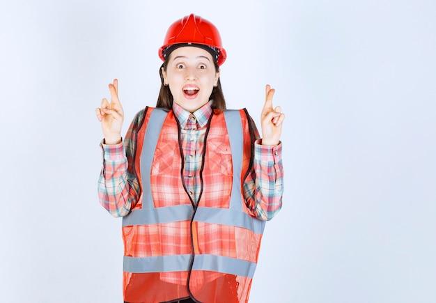 Portret młodego inżyniera piękne kobiece w kasku dając tajny znak.