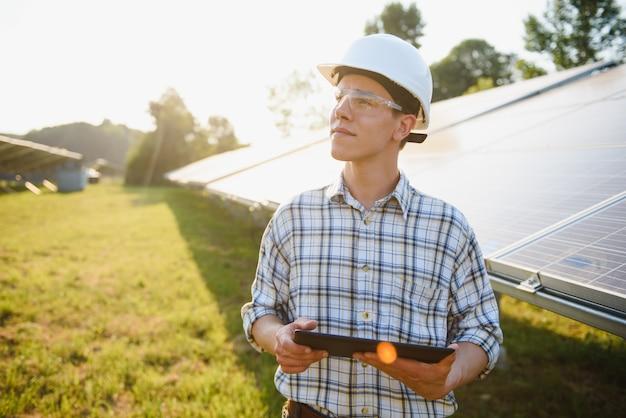 Portret młodego inżyniera sprawdza fotowoltaiczne panele słoneczne